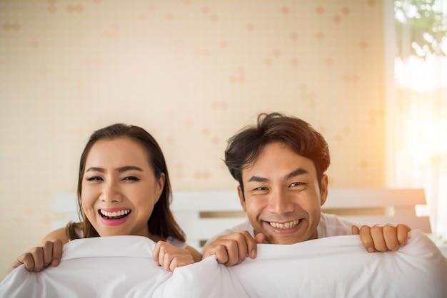 Doux couple jouant sous la couverture sur le lit