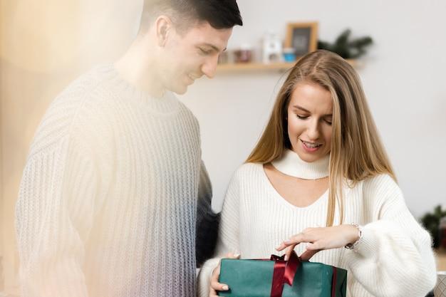 Doux couple ouvrant des cadeaux de noël dans le salon à la maison