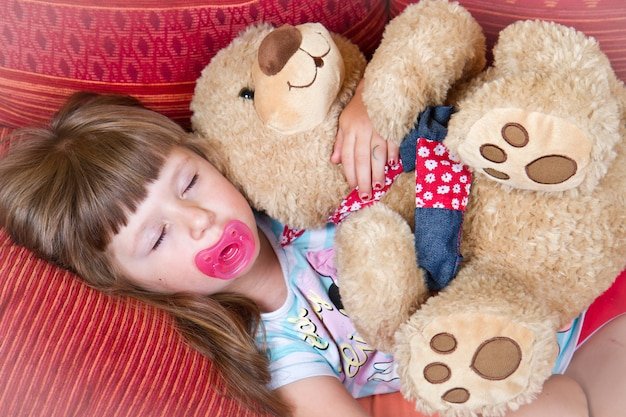 Doux enfant dort avec ours en peluche