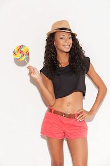 Doux et extrêmement gros. belle jeune femme africaine au chapeau funky tenant une grosse sucette et souriant en se tenant debout sur fond blanc