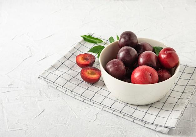 Doux frais délicieux prunes rouges sur bol blanc et serviette table en bois blanc fruits d'été