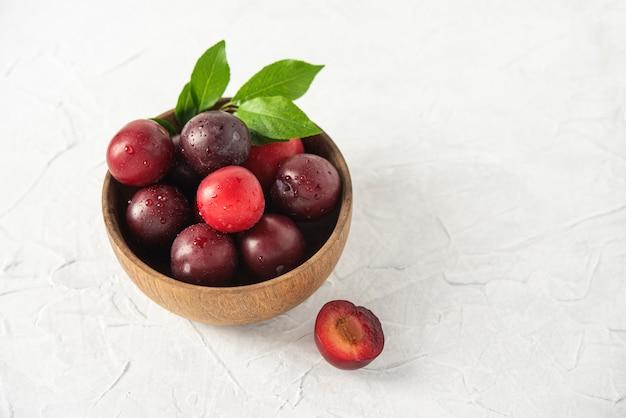 Doux frais délicieux prunes rouges sur un bol table en bois blanc fruits d'été