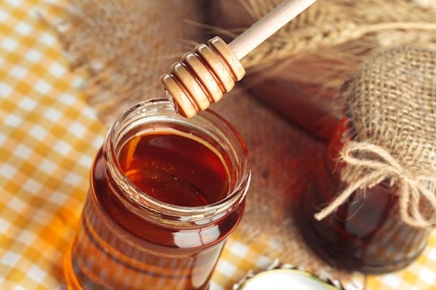 Doux miel en pot de verre sur fond en bois.