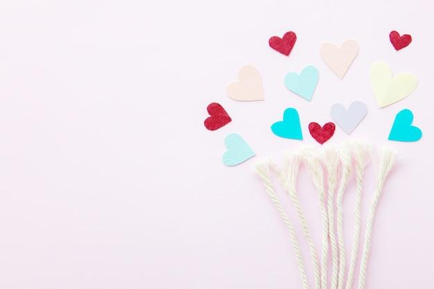 Doux mini coeurs en corde colorée blanche sur fond pastel, arbre de l'amour