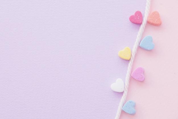 Doux mini coeurs en corde colorée blanche sur fond pastel