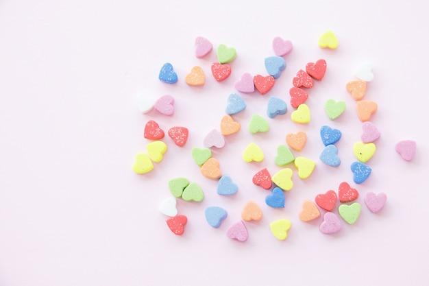Doux mini coeurs en couleurs sur fond pastel