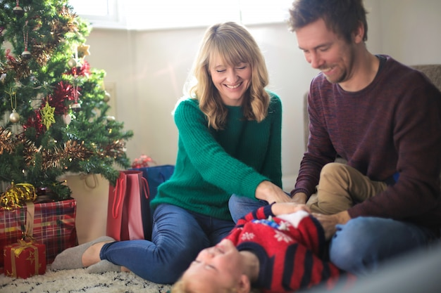 Doux parents chatouillant leur fils, assis devant l'arbre de noël