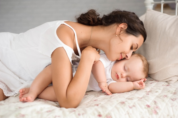 Doux petit garçon dort dans le lit avec sa mère