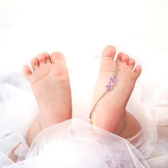 Doux pieds de bébé nouveau-né et bracelet en or blanc