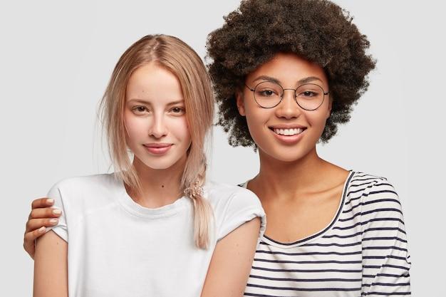 Doux tendre couple de femmes homosexuelles métisses étreindre et avoir des expressions amicales. belle femme afro-américaine tient fermement sa charmante meilleure amie. concept de personnes, d'émotions et d'amitié