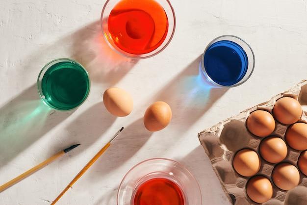 Une douzaine d'œufs dans un carton, des peintures à l'aquarelle usagées.