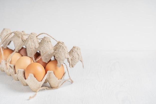 Douzaine d'oeufs de poulet frais brun cru dans une boîte en carton de papier recyclé sur table en bois blanc