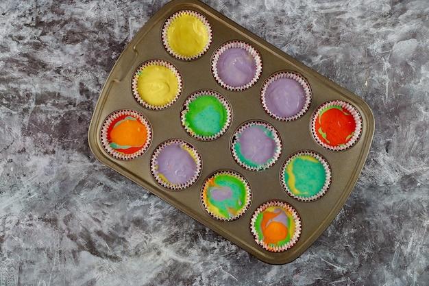 Douze morceaux de cupcakes crus de couleur sur la plaque du four.