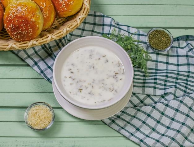 Dovga de soupe caucasienne traditionnelle dans un bol blanc.