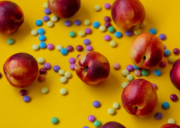Dragées bonbons et pêches sur jaune