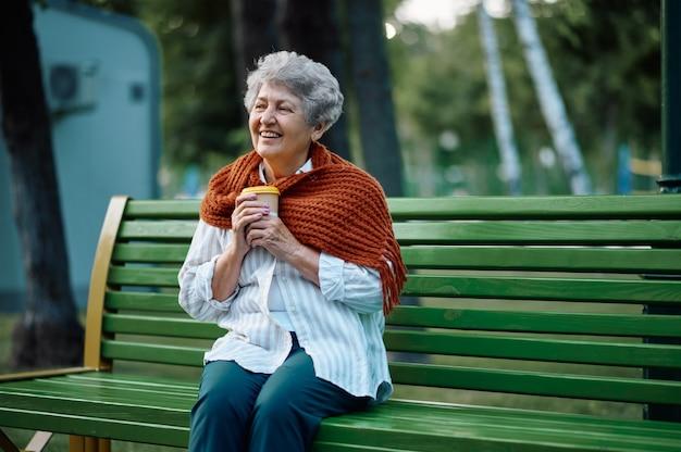 Dranny en écharpe boit du café chaud sur le banc dans le parc d'été. mode de vie des personnes âgées. jolie grand-mère loisirs à l'extérieur, vieille personne de sexe féminin sur la nature