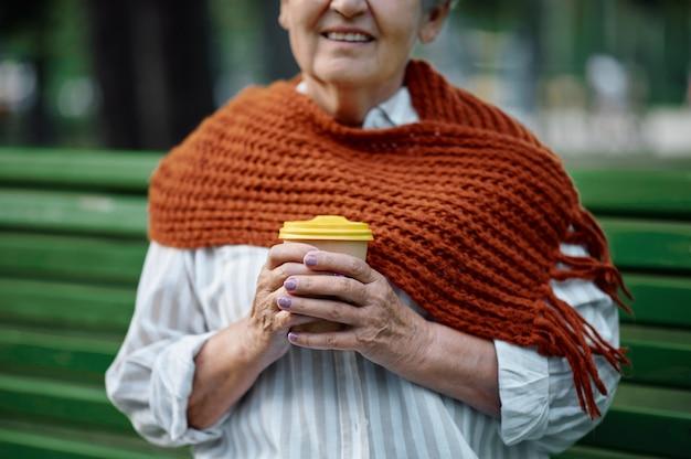 Dranny en écharpe boit du café chaud sur le banc