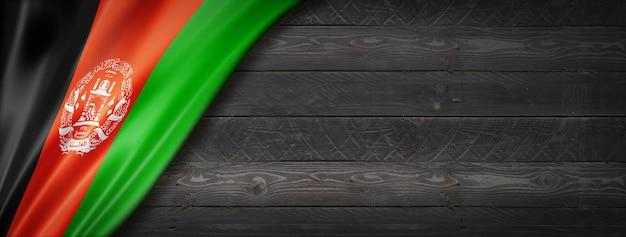 Drapeau de l'afghanistan sur mur en bois noir