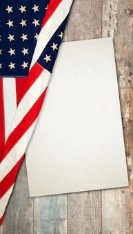 Drapeau américain allongé sur une surface en bois vieilli et rustique avec une carte en papier