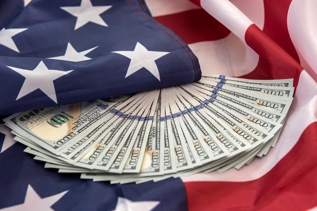 Drapeau américain et argent comptant en dollars comme arrière-plan de l'économie des finances des états-unis