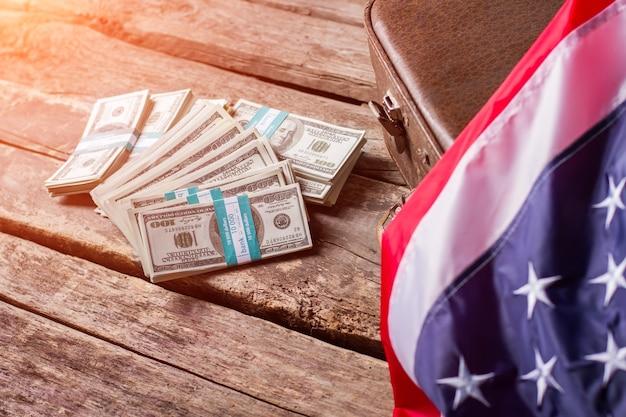 Drapeau américain, argent comptant et valise. paquets d'argent posés à côté de l'étui. prospérité et progrès. travaillez et respectez le pays.