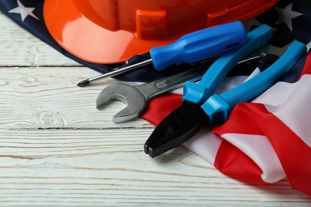Drapeau américain, casque et outils sur bois blanc