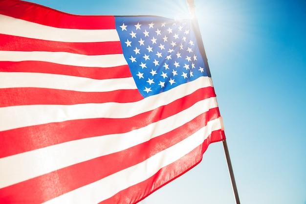 Drapeau américain avec un ciel bleu et la lumière du soleil pour le memorial day ou 4 juillet.