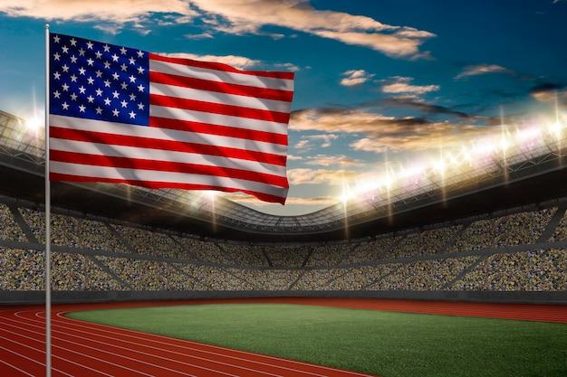 Drapeau américain devant un stade d'athlétisme avec des fans.
