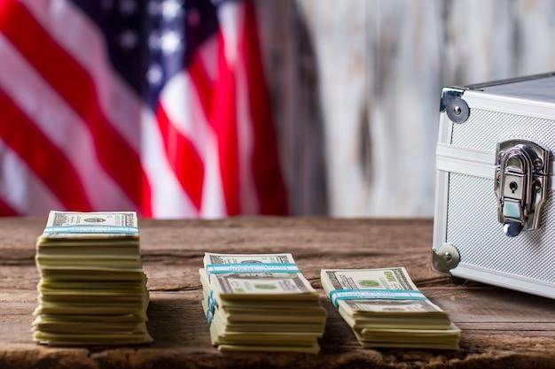 Drapeau américain, dollars et étui. paquets de dollars près de la valise en argent. trouvez votre source de revenus. progrès de l'économie.