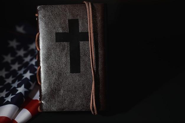 Drapeau américain et livre de la sainte bible sur un fond de miroir. symbole des états-unis et de la religion. bible et drapeau rayé sur fond noir.