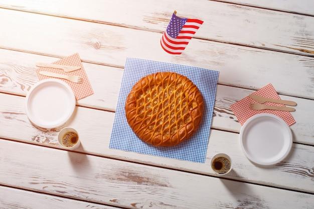 Drapeau américain, tarte et boissons. drapeau de table à côté de la tarte ronde. petit-déjeuner salé au café américain. dessert simple servi avec du café.