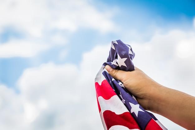 Drapeau américain tenu par une main avec des nuages de fond