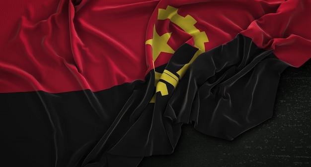 Drapeau de l'angola enroulé sur fond sombre 3d render