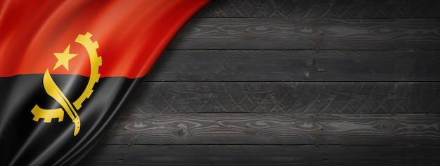 Drapeau de l'angola sur mur en bois noir