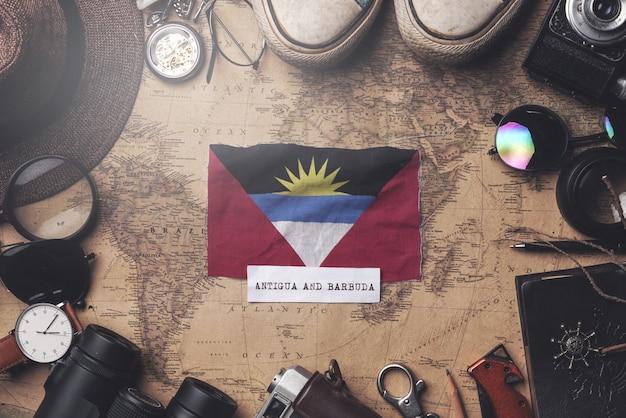 Drapeau d'antigua-et-barbuda entre les accessoires du voyageur sur l'ancienne carte vintage. tir aérien
