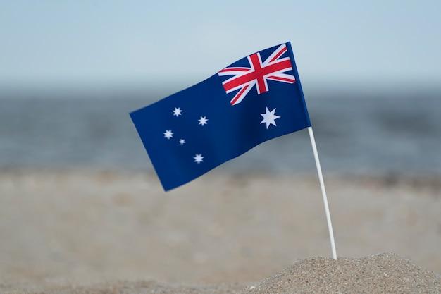 Drapeau australien dans le sable sur la plage. vacances à la mer en australie.