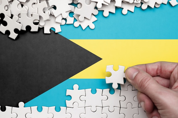 Drapeau des bahamas est représenté sur une table sur laquelle la main humaine plie un puzzle de couleur blanche
