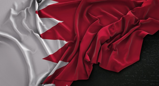 Le drapeau de bahrein est enroulé sur un fond sombre 3d render