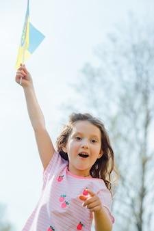 Drapeau bleu-jaune de l'ukraine volant dans le vent dans les mains de la petite fille ukrainienne le jour de l'indépendance de l'ukraine.