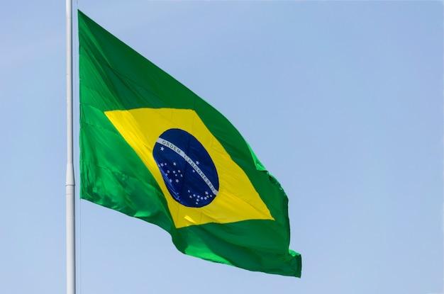 Drapeau brésilien flottant au vent. le drapeau du brésil. ordre et progrès