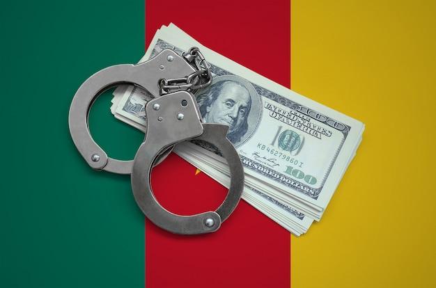Drapeau camerounais avec des menottes et un paquet de dollars. la corruption monétaire dans le pays. crimes financiers