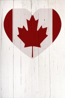 Drapeau canadien en forme de coeur sur une planche de bois blanche