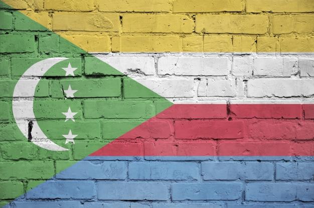 Le drapeau des comores est peint sur un vieux mur de briques