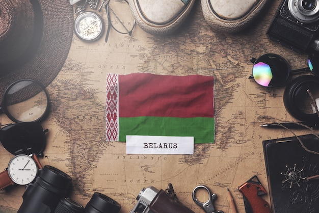 Drapeau du bélarus entre les accessoires du voyageur sur l'ancienne carte vintage. tir aérien