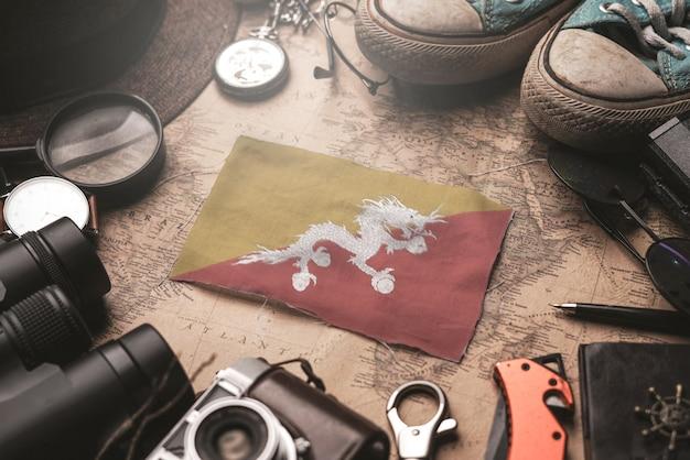 Drapeau du bhoutan entre les accessoires du voyageur sur l'ancienne carte vintage. concept de destination touristique.