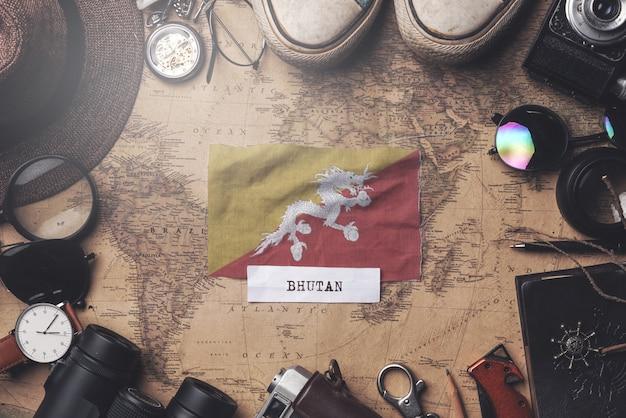Drapeau du bhoutan entre les accessoires du voyageur sur l'ancienne carte vintage. tir aérien