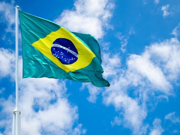 Drapeau du brésil flottant au vent. drapeau brésilien avec ciel bleu et nuages blancs.