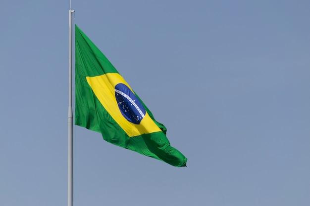 Drapeau du brésil flottant dans le ciel bleu avec des nuages ordre et progrès en portugais brésilien