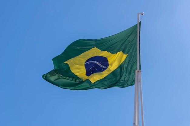 Drapeau du brésil flottant dans le ciel bleu ordre et progrès en portugais drapeau brésilien
