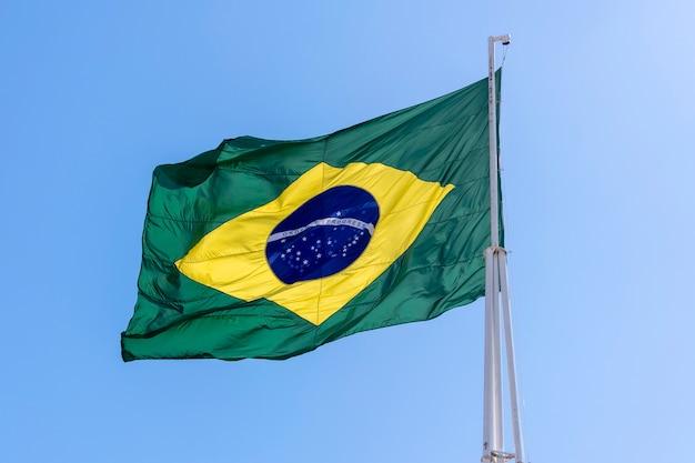 Drapeau du brésil flottant dans le ciel bleu. ordre et progrès en portugais.